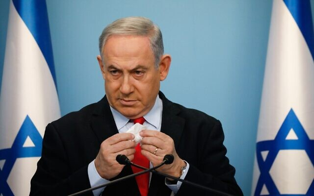 Israeli Prime Minister Benjamin Netanyahu at a Jerusalem news conference encourages citizens to cover their mouths with a tissue when they cough, March 12, 2020. (Olivier Fitoussi/Flash90/via JTA)