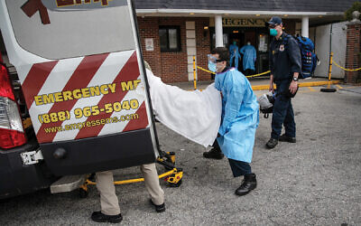 Medics loading a suspected Covid-19 patient from Regency Extended Care Center in Yonkers into an ambulance. Getty Images