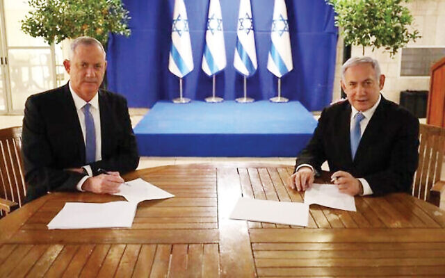 Blue and White leader Benny Gantz, left, and Prime Minister Benjamin Netanyahu signing their unity government agreement Monday. GPO