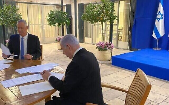 Blue and White leader Benny Gantz (left) and Prime Minister Benjamin Netanyahu sign their unity government agreement on April 20, 2020 (courtesy)