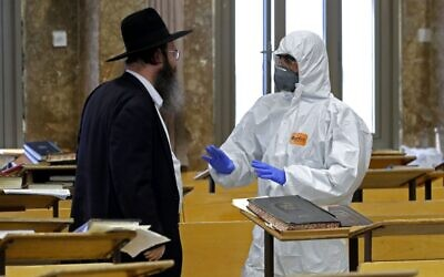 An Israeli police officer, dressed in protective outfit, speaks to an Orthodox Jew at a Yeshiva in the Israeli city of Bnei Brak on April 2, 2020, during a control to insure that social distancing measures imposed by Israeli authorities meant to curb the spread of the novel coronavirus are being respected. JACK GUEZ/AFP via Getty Images