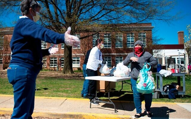 A volunteer directs a woman that received a weeks worth of lunches before the start of Spring break to help families that depended on school lunches during the coronavirus, COVID-19, pandemic. ANDREW CABALLERO-REYNOLDS/AFP via Getty Images