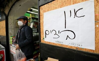 "A shopper wearing a protective mask, precaution against COVID-19 coronavirus disease, exits a food market in Jerusalem on April 6, 2020, while walking past a sign reading in Hebrew ""no eggs"" - Israel is facing a shortage of eggs as people stockpiled the commodity ahead of the Jewish Passover holiday, during which eggs are central piece in dinners. EMMANUEL DUNAND/AFP via Getty Images"