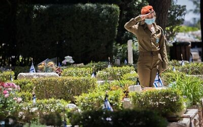 An Israeli soldier salutes fallen comrades at the Mount Herzl military cemetery in Jerusalem hours before the start of Memorial Day, which began April 27, 2020 at sundown. (Yonatan Sindel/Flash90 via JTA)