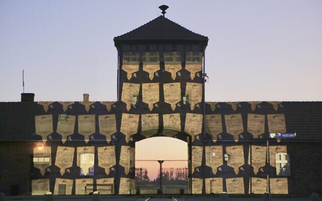 Virtual memorial plaques were projected onto the gates of Birkenau, the former Nazi concentration and extermination camp in Poland, on April 20, 2020. The plaques were uploaded by people across the world to March of the Living's online platform. (March of the Living-Marcin Kozlowski)
