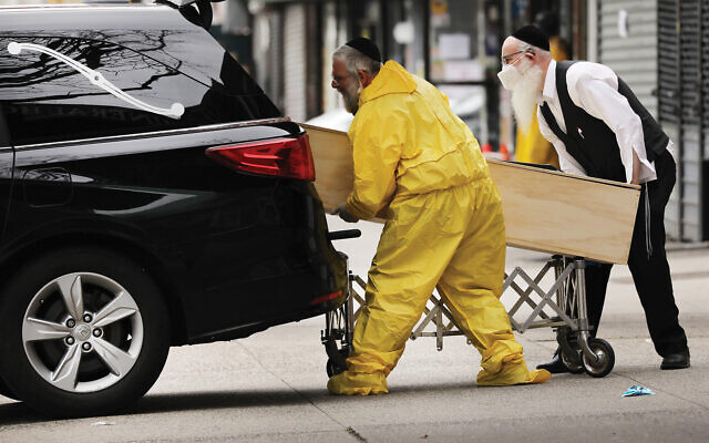 Orthodox men move a wooden casket from a hearse at a funeral home in Borough Park. The neighborhood has been especially hard hit by the coronavirus. Getty Images
