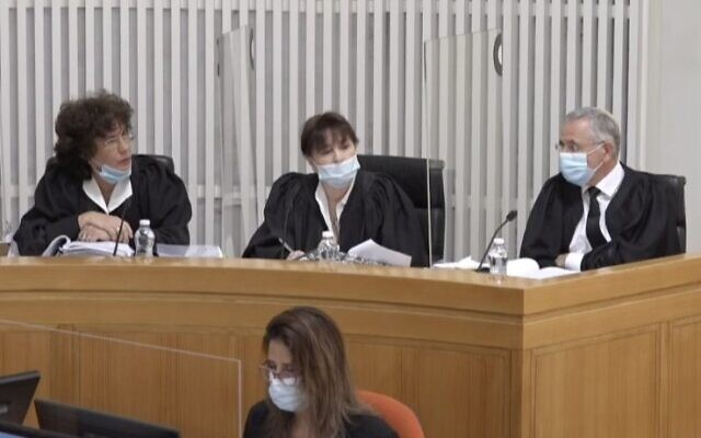 Members of Israel's Supreme Court wore protective masks Sunday, May 3, 2020, as they began discussions over whether Prime Minister Benjamin Netanyahu can form a new government while facing criminal indictments. The court's decision was expected later in the week. (Government Press Office)