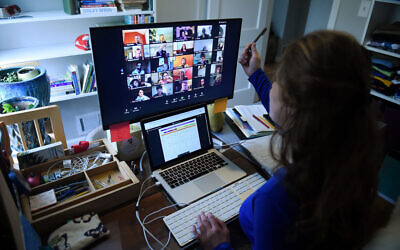 A teacher works from her home, teaching via Zoom, due to the Coronavirus. OLIVIER DOULIERY/AFP via Getty Images