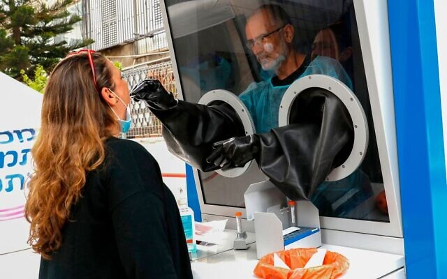 Israel's Maccabi Healthcare services (HMO) install a COVID-19 testing booth which enables medical workers to collect swab samples from individuals in the coastal city of Tel-Aviv, on April 16, 2020. JACK GUEZ/AFP via Getty Images