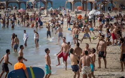 Israelis enjoy the Tel Aviv beach, flouting coronavirus restrictions, as the temperatures rose above 100 degrees throughout the country on May 16, 2020. (Miriam Alster/Flash90 via JTA)