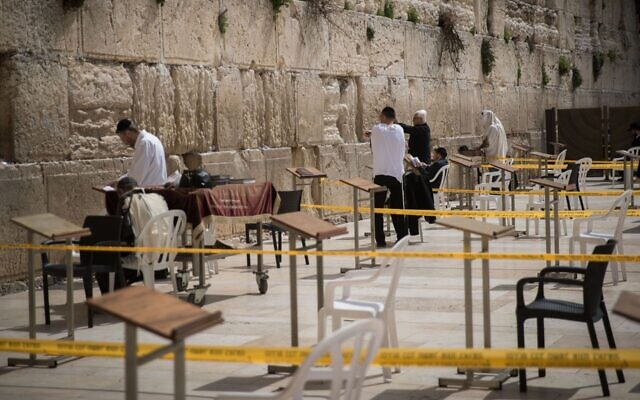 Worshippers at the Western Wall pray in enclosed areas meant for 10 people at a time in order to prevent the spread of coronavirus on March 15, 2020 (Yonatan Sindel/Flash90/via JTA)