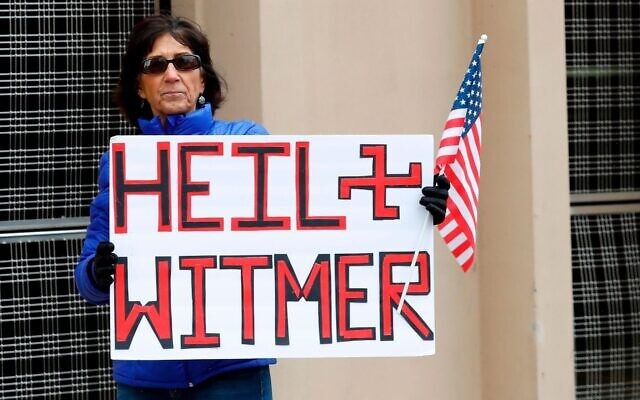 A sign comparing Michigan Gov. Gretchen Whitmer to Adolf Hitler during a protest in Lansing of her extension of stay-at-home orders to fight the coronavirus crisis, April 15, 2020. (Jeff Kowalsky/AFP via Getty Images)