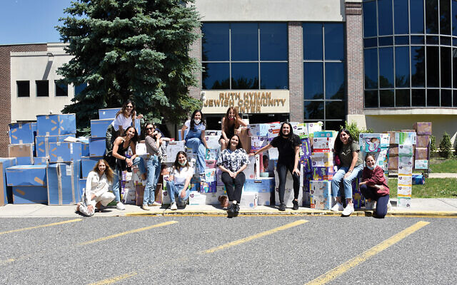 Volunteers, mostly members of the UJA-Federation's Young Sephardic Division, pose outside the JCC of the Jersey Shore in Deal with baby goods they collected for families hit hard by the pandemic. (Diane Mishan)