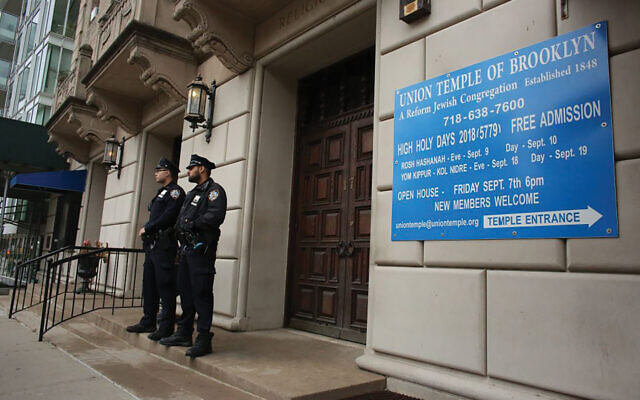 NYPD officers stand guard at the door of the Union Temple of Brooklyn, Nov. 2, 2018. Kena Betancur/AFP via Getty Images