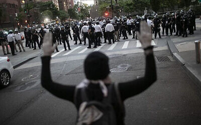 A protester raises her hands as police start to arrest demonstrators refusing to get off the streets during an imposed curfew while marching in a solidarity rally calling for justice over the death of George Floyd, on June 2, 2020, in New York. (AP Photo/Wong Maye-E via Jewish News/via The Times of Israel)