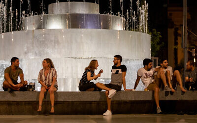 Israelis gather at Dizengoff Square in Tel Aviv with drinks from home and from the surrounding bars as lockdown restrictions were partly removed, May 18, 2020. (Guy Prives/Getty Images via JTA)