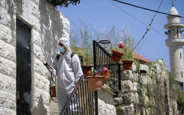Palestinian workers clean streets and homes in the West Bank city of Nablus to prevent the spread of the coronavirus, April 3 2020,. (Nasser Ishtayeh/Flash90 via JTA)