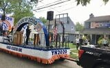 Yeshivat Noam, a k-8 Modern Orthodox Jewish day school in Paramus, NJ, honored graduates with a parade float driven to their homes. Above, Rabbi Chaim Hagler, head of school. greets a graduate in Teaneck, NJ. (Jewish Week)