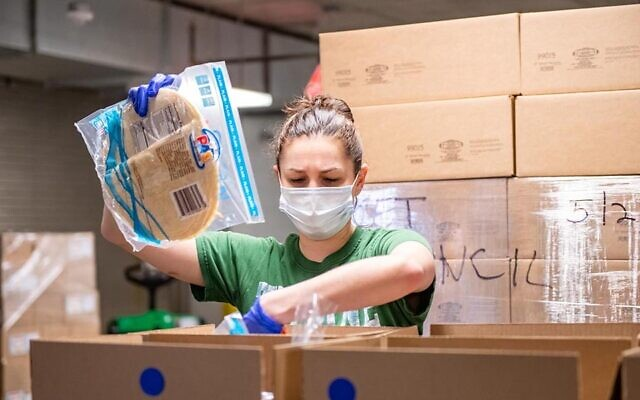 A volunteer packs groceries at the Met Council's warehouse in Brooklyn. Volunteers there assemble more than 1,200 packages of groceries for Holocaust survivors each week. (Courtesy of Met Council)