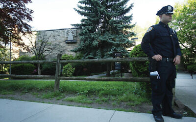 A police officer guards a synagogue in suburban New York. Getty Images