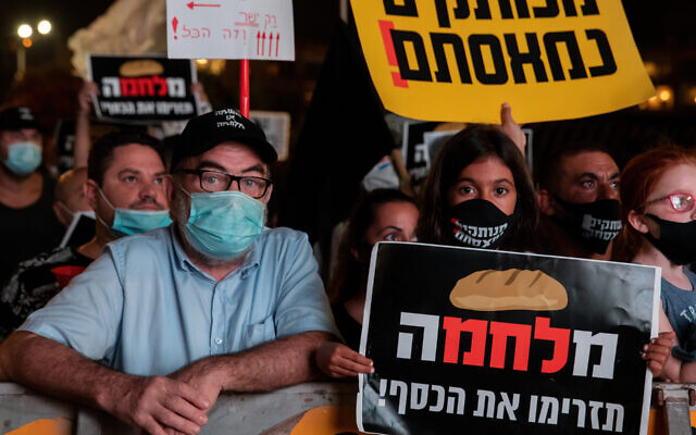 People hold placards during a protest at Rabin Square on July 11, 2020 in Tel Aviv. Following a rise in the cases of Covid-19, over 10,000 people protested about a perceived mishandling of the coronavirus pandemic and called for the compensation promised by the government to be paid out more quickly. )Guy Prives/Getty Images)