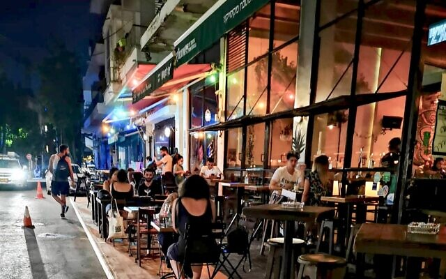 The Tel Aviv-Yafo Municipality has launched a creative solution to enable restaurants and bars to extend their outdoors seating areas to ensure social distancing required by the Covid-19 pandemic. Sidewalk-level platforms permit restaurants and bars to add dozens of outdoors tables and chairs. (Yonatan Bendiger)