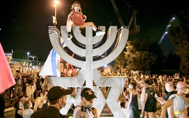 Thousands, including a woman who removed her shirt and sat topless at the top of a menorah sculpture, gathered in Jerusalem to protest Prime Minister Benjamin Netanyahu and the actions of his government, July 21, 2020. (Olivier Fitoussi/Flash90 via JTA)