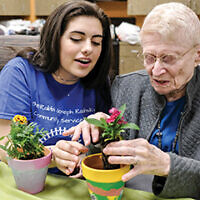 Beren Academy student Dina Kirshner and Medallion resident Marcene Goldman plant flowers together at a pre-pandemic Better Together event in Houston. Ari Kellerman