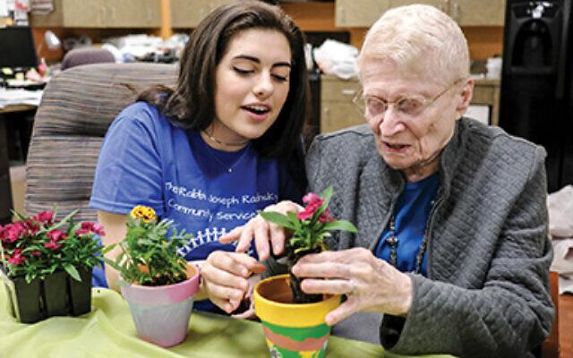 Beren Academy student Dina Kirshner and Medallion resident Marcene Goldman plant flowers together at a pre-pandemic Better Together event in Houston. Ari Kellerman