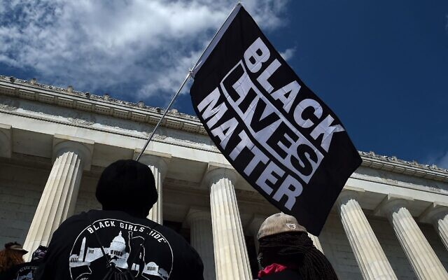 "A person holds a Black Lives Matter flag during the ""Commitment March: Get Your Knee Off Our Necks"" protest against racism and police brutality at the Lincoln Memorial on Aug. 28, 2020, in Washington DC. (OLIVIER DOULIERY/POOL/AFP via Getty Images)"