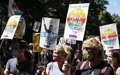"""Counter-protesters in Berlin on Aug. 1, 2020, hold signs with slogans like """"No place for Nazis"""" at rally supported by neo-Nazi groups to demand an end to coronavirus restrictions. The far-right rally drew more than 20,000 people. (Photo: Fabian Sommer/picture alliance via Getty Images)"""