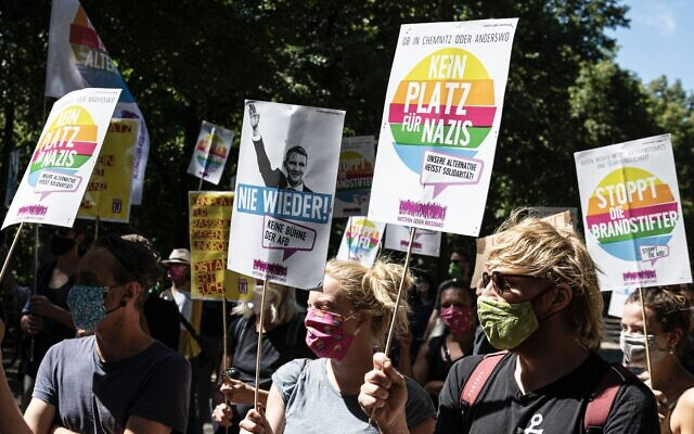 "Counter-protesters in Berlin on Aug. 1, 2020, hold signs with slogans like ""No place for Nazis"" at rally supported by neo-Nazi groups to demand an end to coronavirus restrictions. The far-right rally drew more than 20,000 people. (Photo: Fabian Sommer/picture alliance via Getty Images)"