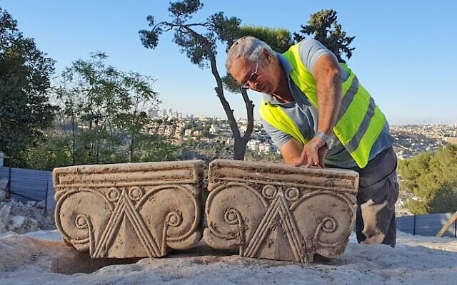An archaeologist at Jerusalem's City of David excavation shows off recently discovered column fragments from a villa built in the period between the days of the biblical kings Hezekiah and Josiah. (Yoli Schwartz/Israel Antiquities Authority)