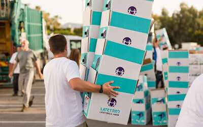 Latet volunteers pack Rosh Hashanah food boxes for impoverished families affected by the pandemic at the organization's logistics center in the Har Tuv industrial area in Beit Shemesh. (https://www.latet.org.il/)