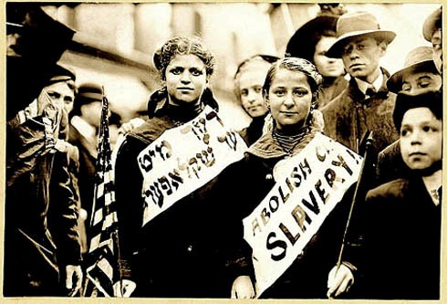 """Marchers bear signs reading """"Abolish [Child] Slavery"""" in English and Yiddish, probably taken during May 1, 1909 labor parade in New York City. (George Grantham Bain Collection, Library of Congress via My Jewish Learning)"""