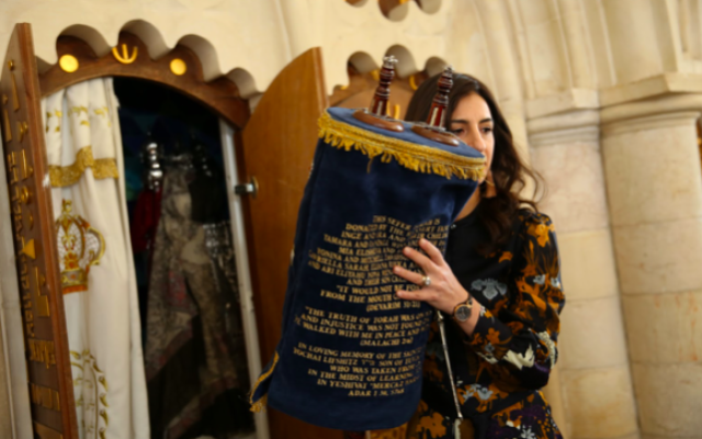 Rabba Dina Brawer removes the Torah from the ark at her son's bar mitzvah.