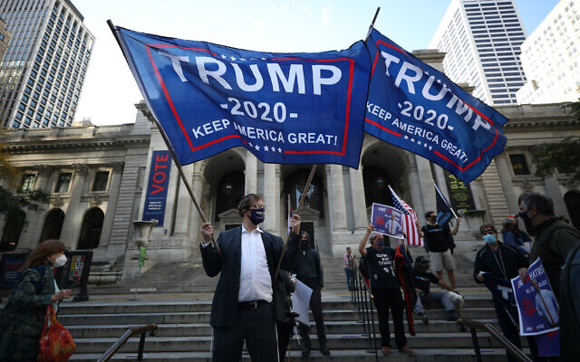 A demonstrator waves a Trump flag  in front of the New York Public Library on 5th Ave. at a protest by Orthodox Jews against Covid-19 restrictions, Oct. 15, 2020. (Photo by Tayfun Coskun/Anadolu Agency via Getty Images)