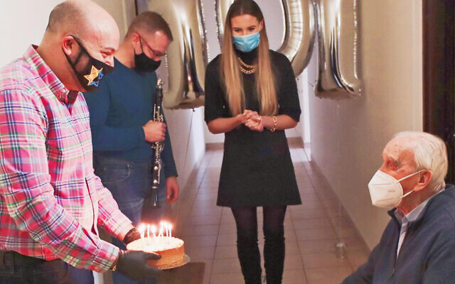 HONORING A RESCUER: Jozef Walaszczyk, right, receives a cake on his 101st birthday in Warsaw, Poland on Nov. 12, 2020. Dozens of people from 49 countries delivered filmed birthday greetings for Walaszczyk, who rescued his Jewish girlfriend and 50 others during the Holocaust. He also fought the Germans as part of the underground, smuggling allied troops across borders. (From the Depths)