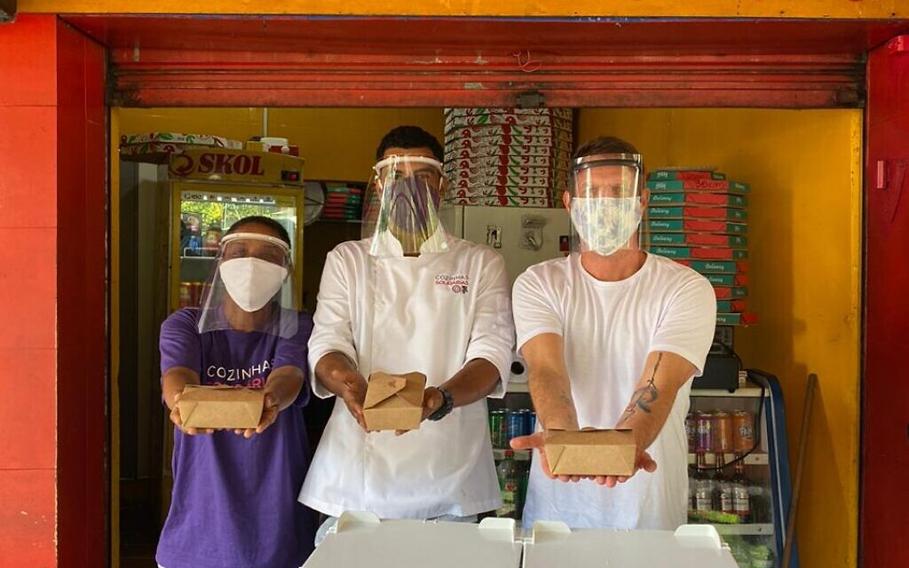 David Hertz, right, and chefs help distribute free meals at one of his network of Solidarity Kitchens, a home-based response to food insecurity during the pandemic in Brazil. (Gastromotiva)