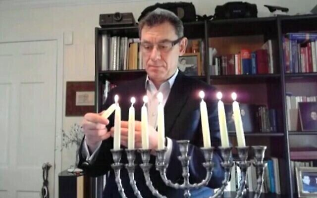 Pfizer CEO Albert Bourla, the Greek son of Holocaust survivors,  lights the Chanukah candles at a virtual ceremony organized by the Isaeli embassy in Washington, on December 16, 2020. (Screen capture/Israeli Embassy in DC)