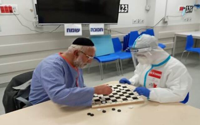 A patient at Herzog Hospital's Covid Isolation Unit in Jerusalem plays checkers with a staff member wearing protective gear. Israel's first batch of Pfizer vaccines arrived on Wednesday as the country began to gear up for a mass vaccination effort to bring the coronavirus pandemic under control. (Courtesy)