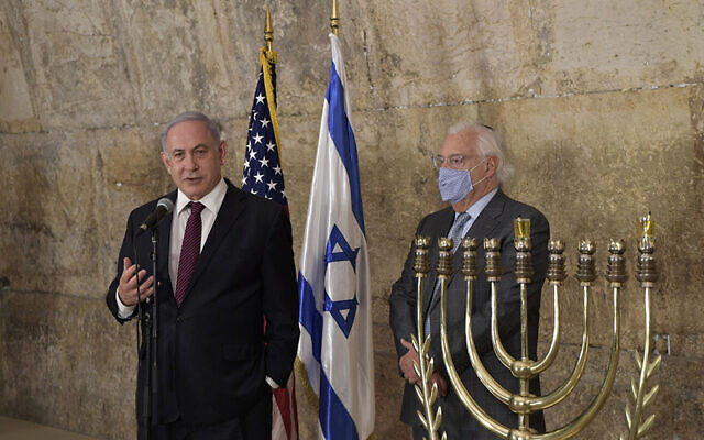 Israeli Prime Minister Benjamin Netanyahu discusses the historic normalization deal with Morocco at a Western Wall ceremony to light the first Chanukah candle, as US Ambassador to Israel David Friedman looks on, Dec. 10, 2020. (Kobi Gideon/GPO)