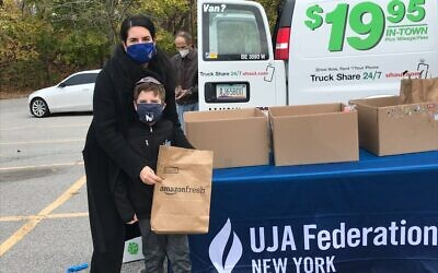 Families pack supplies destined for the Bronx JCC food pantry at the UJA Westchester Emergency Food Drive, Nov. 17, 2020. (UJA-Federation of New York)