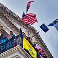 Trump supporters wave flags at the U.S. Capitol on Jan. 6, 2021, as others overwhelmed police and broke into the building. (Brett Davis/Flickr Commons)