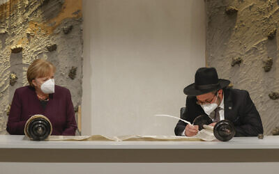 LETTER PERFECT: German Chancellor Angela Merkel watches Rabbi Shaul Nekrich complete the historic Sulzbach Torah Scroll at the Reichstag in Berlin, in an event marking Holocaust Remembrance Day, Jan. 27, 2021. The 18th-century Torah, which survived the Kristallnacht pogrom in 1938 and lay unnoticed for decades in a cabinet in a synagogue in Amberg, Bavaria, was restored thanks to a 45,000-euro donation from the German federal government. (Odd Andersen/Pool/Getty Images)