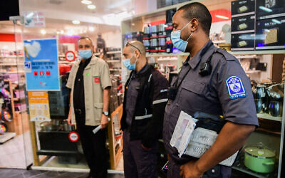 Israeli police officers inspect a mall in the city of Bat Yam that opened in violation of COVID-19 lockdown restrictions, Feb. 11, 2021. Israel's aggressive vaccination drive has become a national source of pride, but it has not yet heralded the return to pre-pandemic times that many had expected. (Avshalom Sassoni/Flash90)