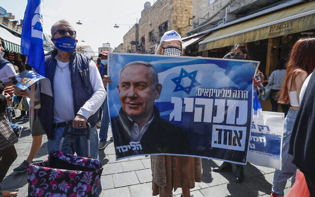 Supporters of Israeli Prime Minister Benjamin Netanyahu's Likud party lift a banner depicting him at Mahane Yehuda market in Jerusalem, March 19, 2021. Israelis go to the polls tomorrow for the fourth time in two years. (Emmanuel Dunand/AFP via Getty Images)