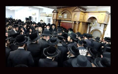 Hundreds of men crowded into a Borough Park study hall for the funeral of Rabbi Yechezkel Roth, Sunday afternoon, March 7, 2021. (Screenshot from BoroPark24)
