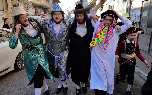 Men dressed in costumes celebrate Purim in the Mea Shearim neighborhood of Jerusalem, Feb. 28, 2021. (Menahem Kahana/AFP via Getty Images)