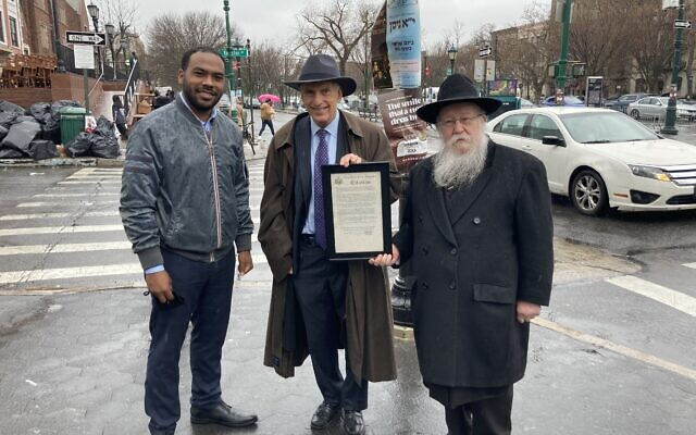 BIRTHDAY GREETINGS: Justin Turner, an aide to State Senator Zellnor Myrie; Assemblyman David Weprin, and Rabbi Shmuel Butman, director of the Lubavitch Youth Organization, commemorated the 119th anniversary of the birth of the late Lubavitcher Rebbe, Rabbi Menachem M. Schneerson, at a ceremony at the corner of Kingston Ave. and Eastern Parkway in Crown Heights, March 25, 2021. (Courtesy)